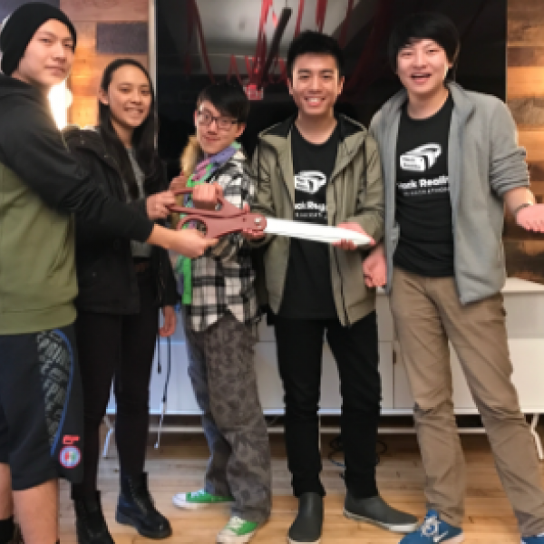 photo of students holding a large pair of scissors