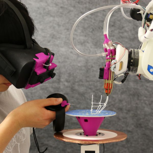 Student interacting with 3D printer wearing augmented reality visor