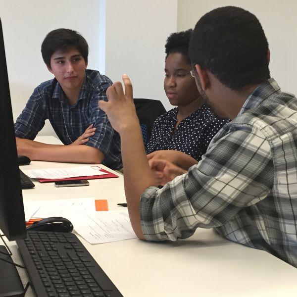 Three SoNIC participants discuss a coding challenge